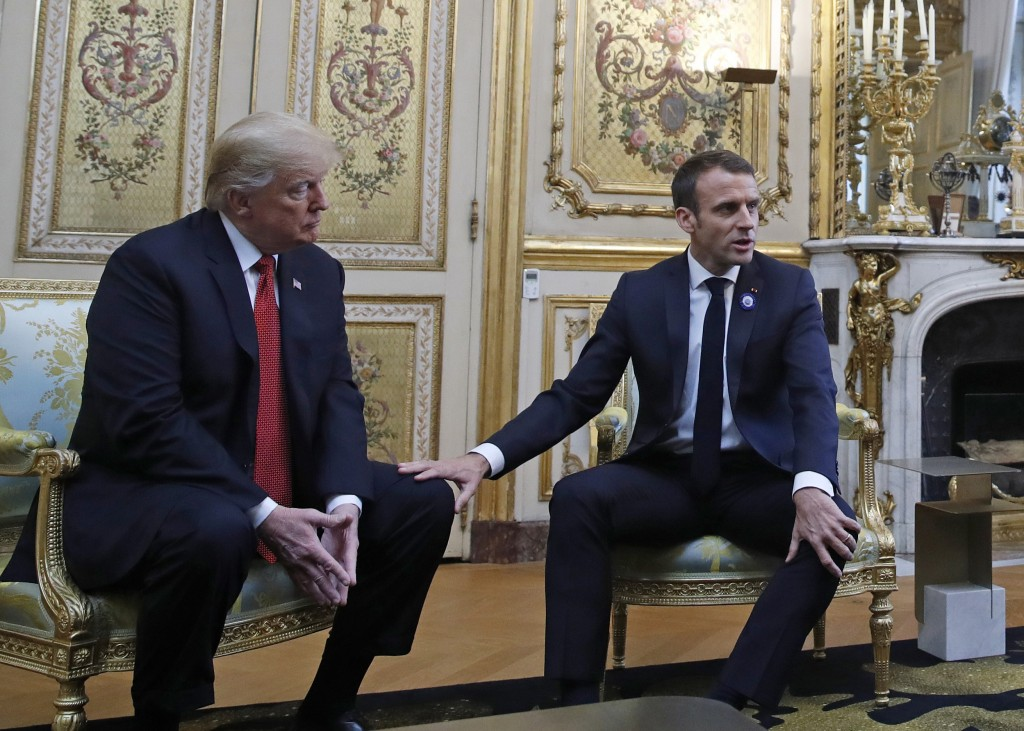 French President Emmanuel Macron touches the knee of President Donald Trump during their meeting inside the Elysee Palace in Paris Saturday Nov. 10, 2