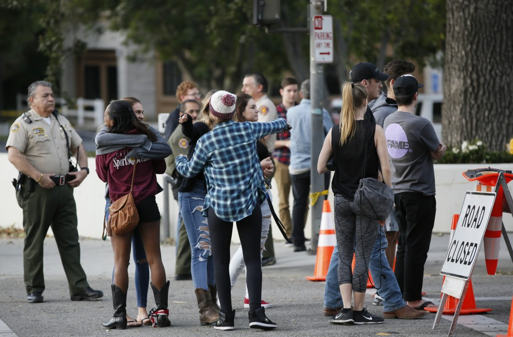 People hug as they arrive to recover their vehicles parked in the parking lot the Borderline Bar & Grill bar in Thousand Oaks, Calif., Friday, Nov. 9,...