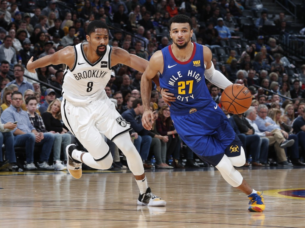 Denver Nuggets guard Jamal Murray, right, drives the lane past Brooklyn Nets guard Spencer Dinwiddie in the first half of an NBA basketball game, Frid