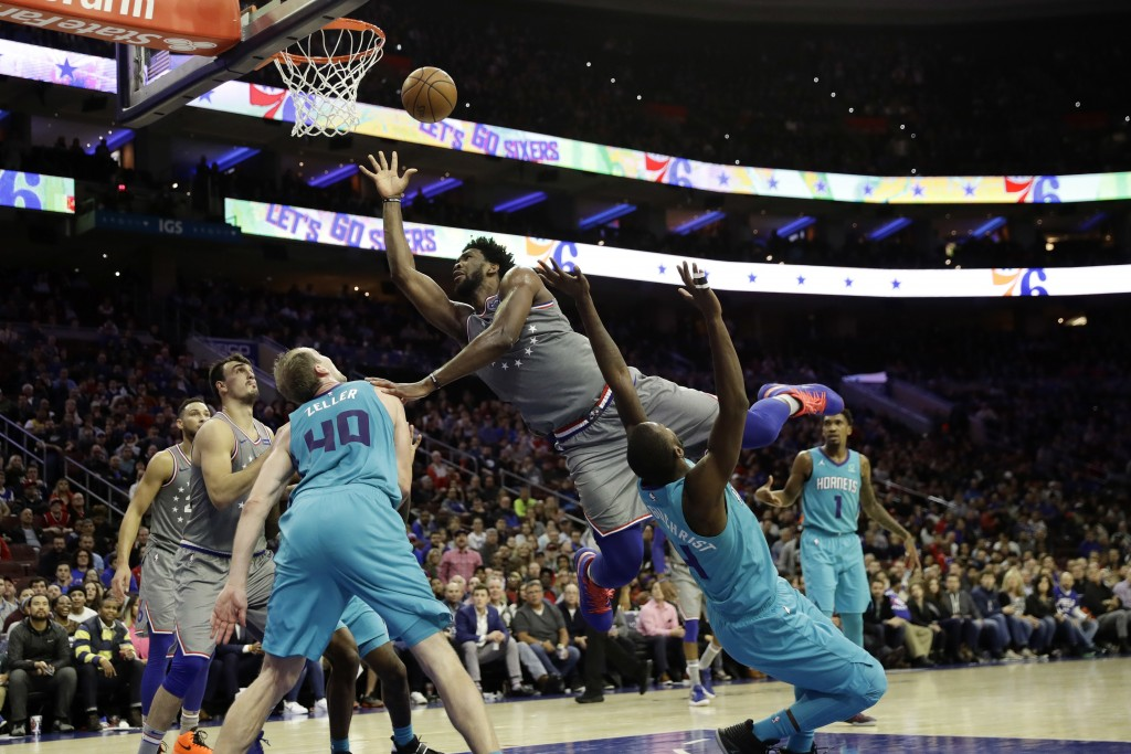 Philadelphia 76ers' Joel Embiid, center, tries to get a shot past Charlotte Hornets' Michael Kidd-Gilchrist, right, and Cody Zeller during the second