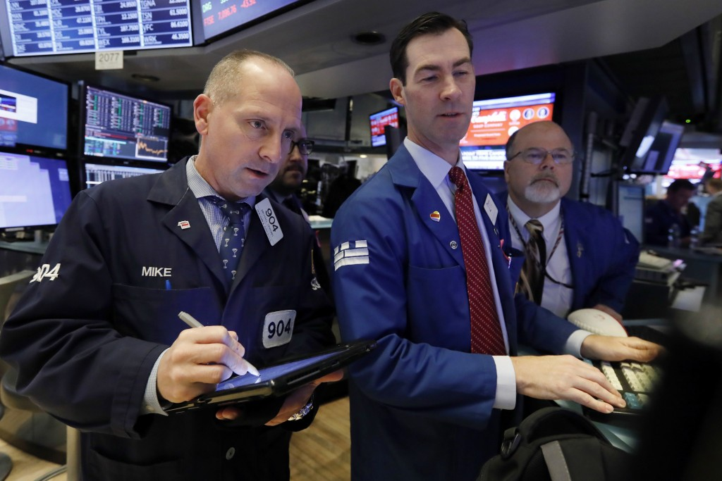 Trader Michael Urkonis. left, works with specialists John McNierney, center, and Douglas Johnson on the floor of the New York Stock Exchange, Friday,