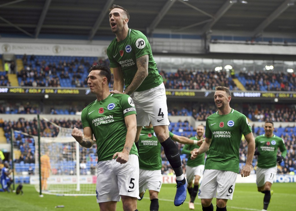 Brighton & Hove Albion's Lewis Dunk, left, celebrates scoring his side's first goal of the game during the English Premier League soccer match between