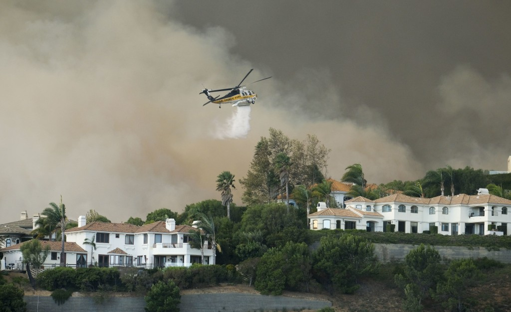 A helicopter drops water on a brush fire behind homes during the Woolsey Fire in Malibu, Calif., Friday, Nov. 9, 2018. A fast-moving wildfire in South