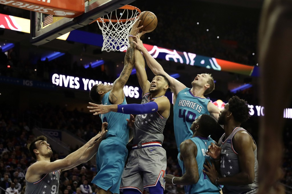Philadelphia 76ers' Ben Simmons, center, tries to get a shot past Charlotte Hornets' Miles Bridges, left, and Cody Zeller during the second half of an