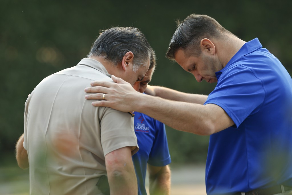 Ventura County Sheriff's Office Capt. Garo Kuredjian, left, embraces chaplains with the Billy Graham Rapid Response Team (RRT) as they pray near the s