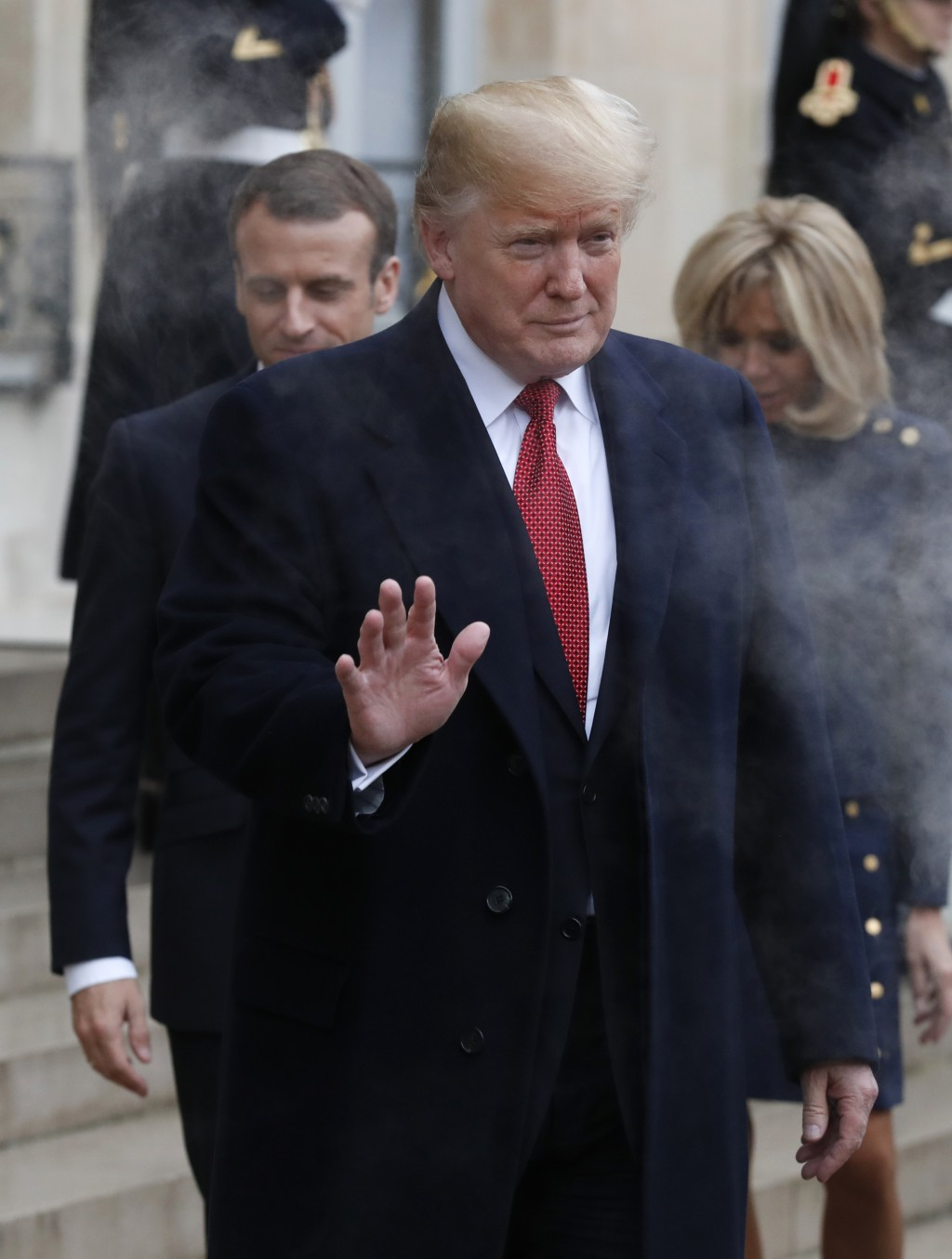 U.S President Donald Trump, followed by French President Emmanuel Macron, left, and his wife Brigitte, right, gestures outside the Elysee Palace after