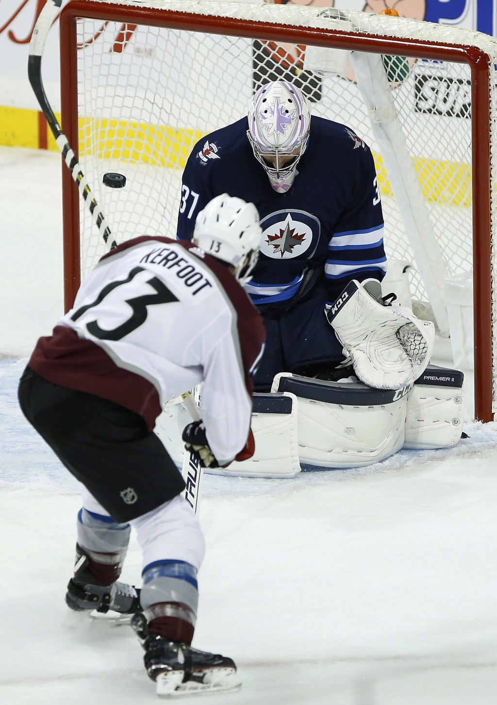 Winnipeg Jets goaltender Connor Hellebuyck (37) saves the shot by Colorado Avalanche's Alexander Kerfoot (13) and it goes wide during the first period