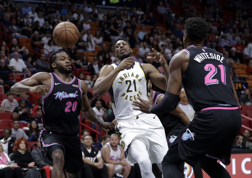 Indiana Pacers forward Thaddeus Young (21) loses control of the ball as Miami Heat forward Justise Winslow (20) and center Hassan Whiteside (21) defen