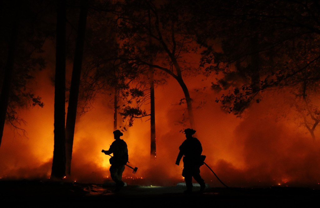 Firefighters work on a controlled burn at a wildfire, Friday, Nov. 9, 2018, in Magalia, Calif. (AP Photo/John Locher)