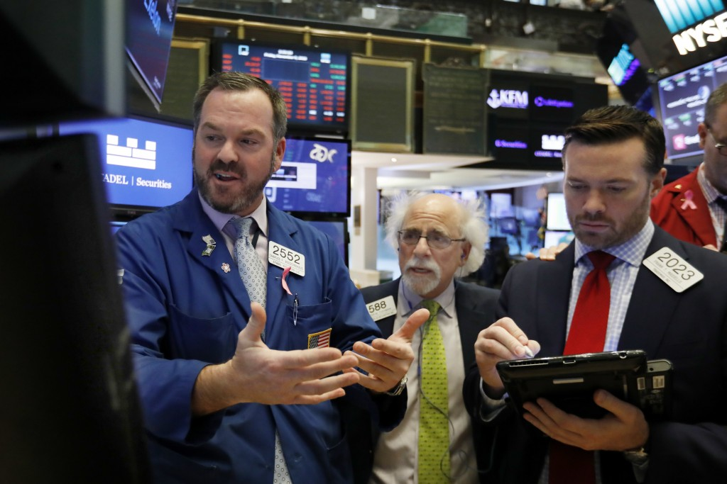 Specialist Charles Boeddinghaus, left, works with traders Peter Tuchman, center, and Frank Masiello on the floor of the New York Stock Exchange, Frida
