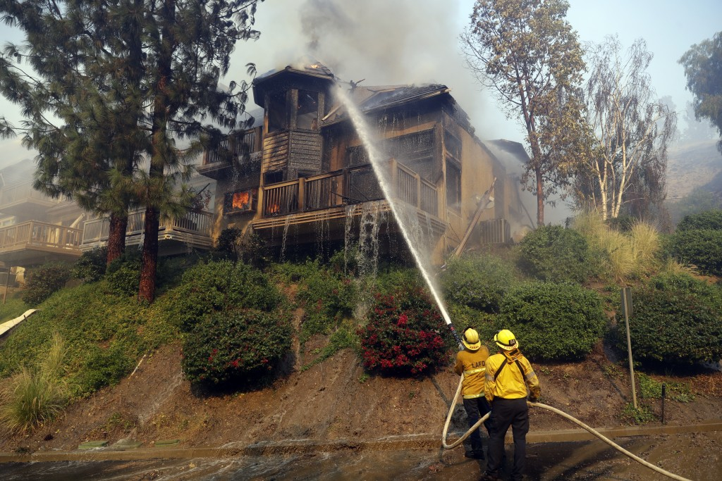 Firefighters hose down a burning home Friday, Nov. 9, 2018, in Westlake Village , Calif. (AP Photo/Marcio Jose Sanchez)