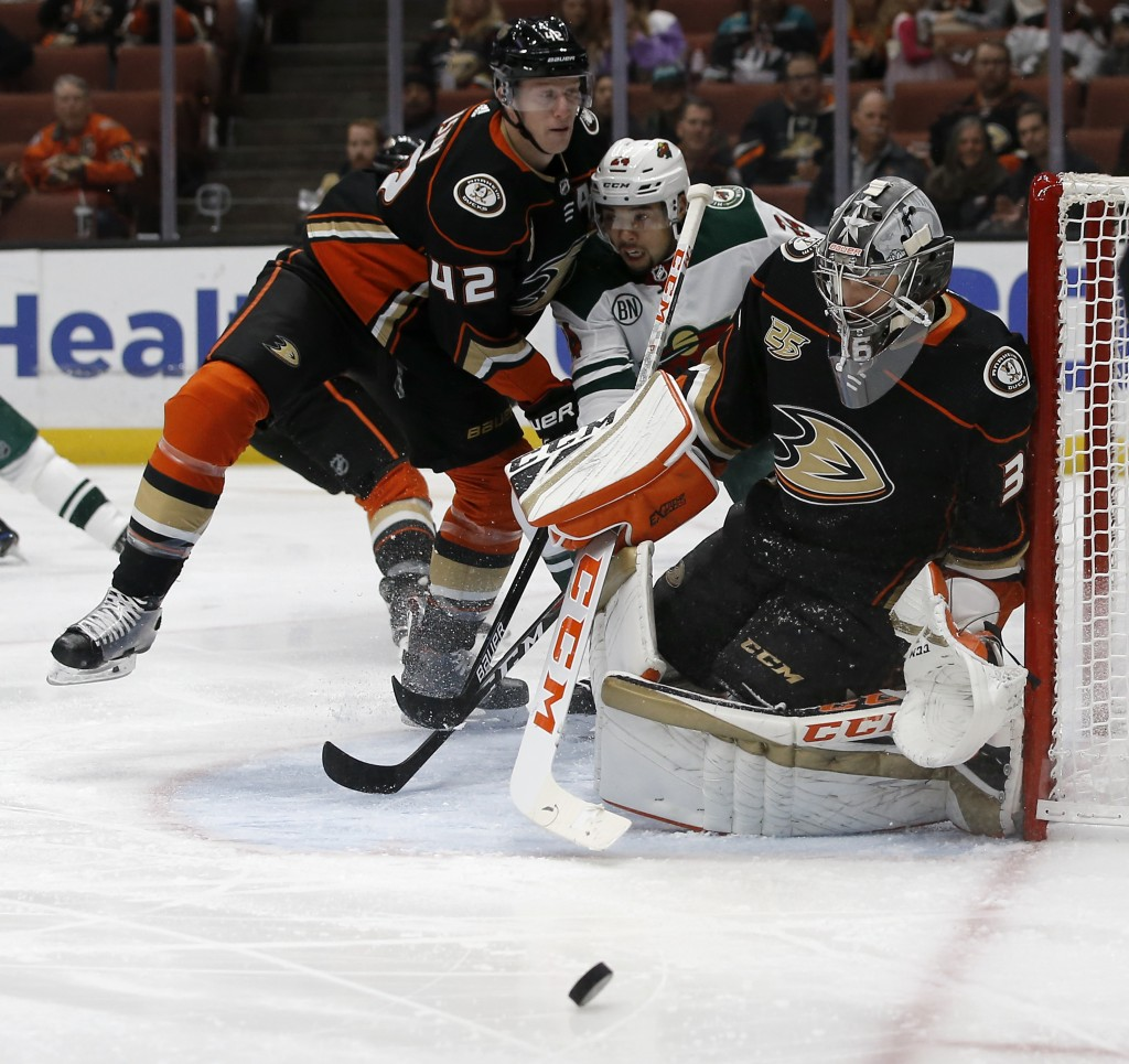 Anaheim Ducks goaltender John Gibson, right, deflects a shot as defenseman Josh Manson, left, squeezes Minnesota Wild defenseman Matt Dumba from getti
