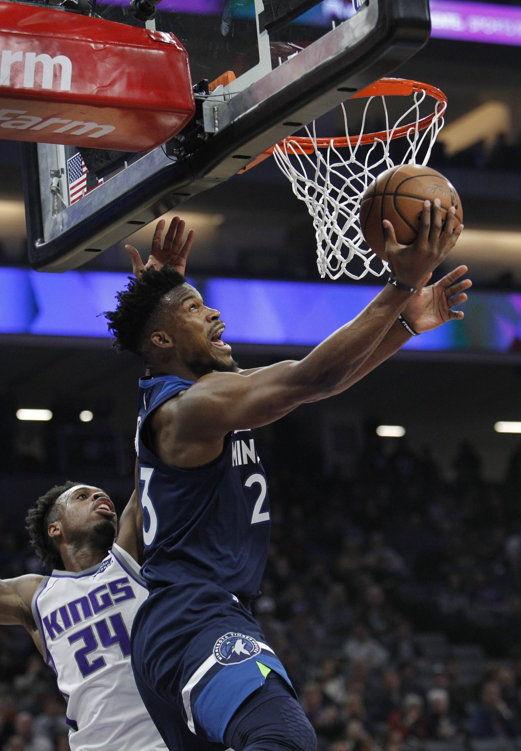 Minnesota Timberwolves guard Jimmy Butler (23) gets around Sacramento Kings guard Buddy Hield (24) for a basket during the first half of an NBA basket