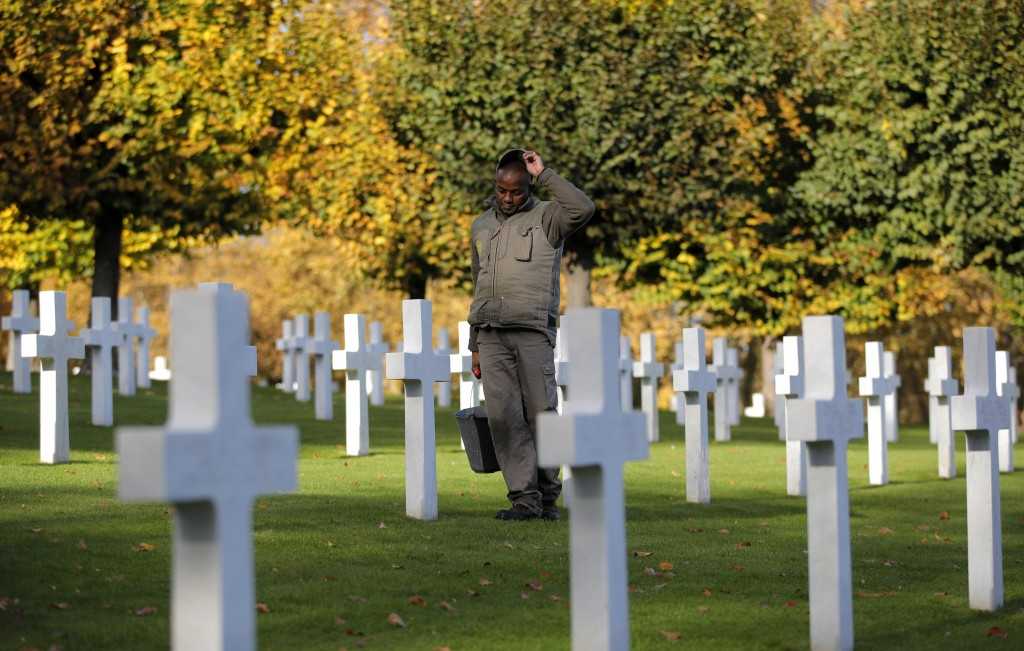 A cemetery employee walks between graves of American serviceman killed during WWI ahead of celebrations of the WWI centenary at the American Cemetery