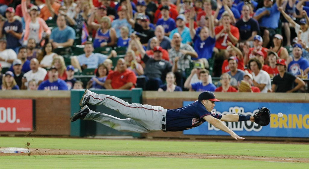 FILE - In this Saturday, July 9, 2016, file photo, Minnesota Twins first baseman Joe Mauer dives for a bad throw from second baseman Brian Dozier duri