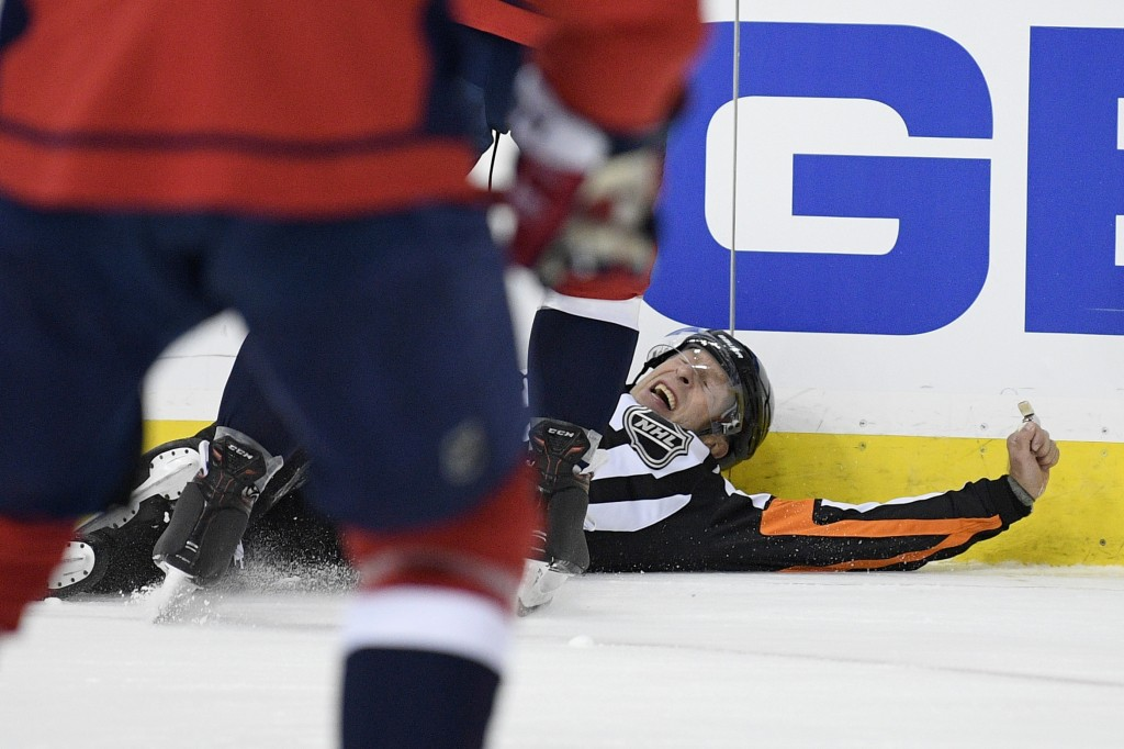 Referee Brad Meier falls to the ice during the first period of an NHL hockey game between the Washington Capitals and the Columbus Blue Jackets, Frida