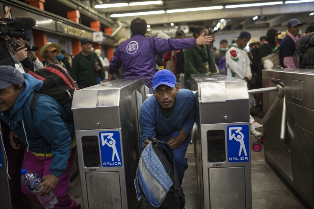 A Central American migrant bypasses a subway turnstile after leaving the temporary shelter at the Jesus Martinez stadium, in Mexico City, Friday, Nov.