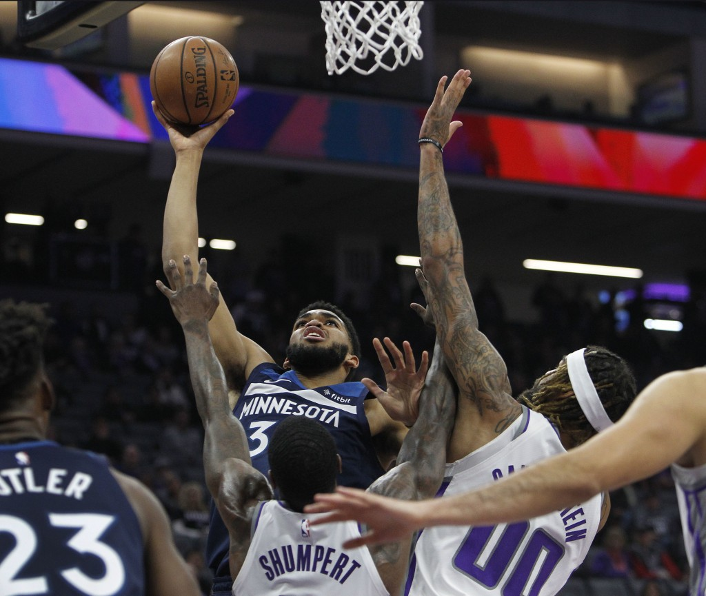 Minnesota Timberwolves center Karl-Anthony Towns (32) shoots over Sacramento Kings guard Iman Shumpert (9) and Sacramento Kings center Willie Cauley-S
