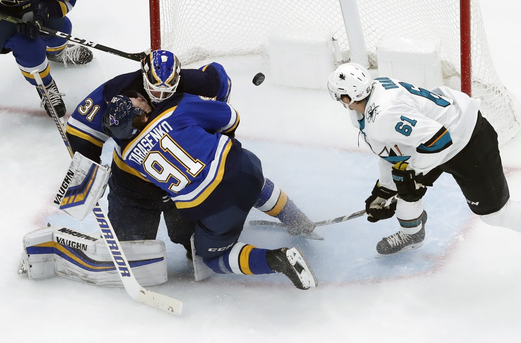 St. Louis Blues' Vladimir Tarasenko (91), of Russia, collides with teammate, goaltender Chad Johnson, as San Jose Sharks' Justin Braun (61) keeps an e...