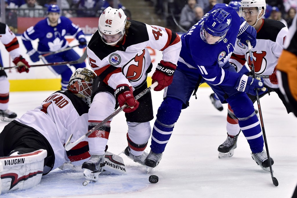 Toronto Maple Leafs left wing Zach Hyman (11) tries to put the puck past New Jersey Devils goaltender Keith Kinkaid (1) as Devils' Sami Vatanen (45) d