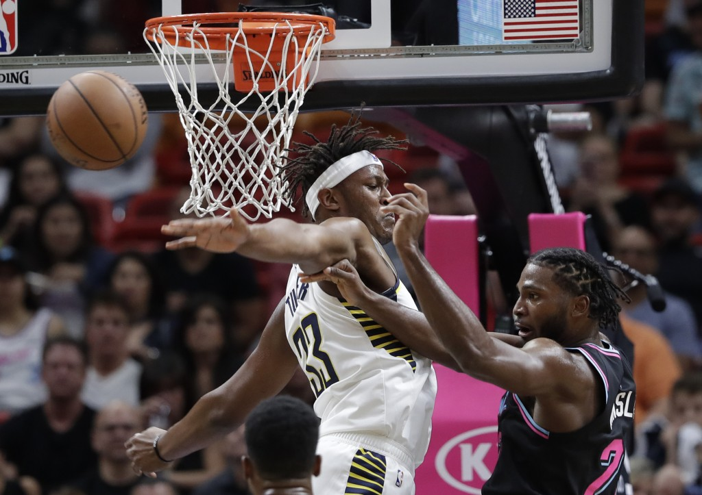 Miami Heat forward Justise Winslow, right, passes the ball as Indiana Pacers center Myles Turner (33) defends during the first half of an NBA basketba