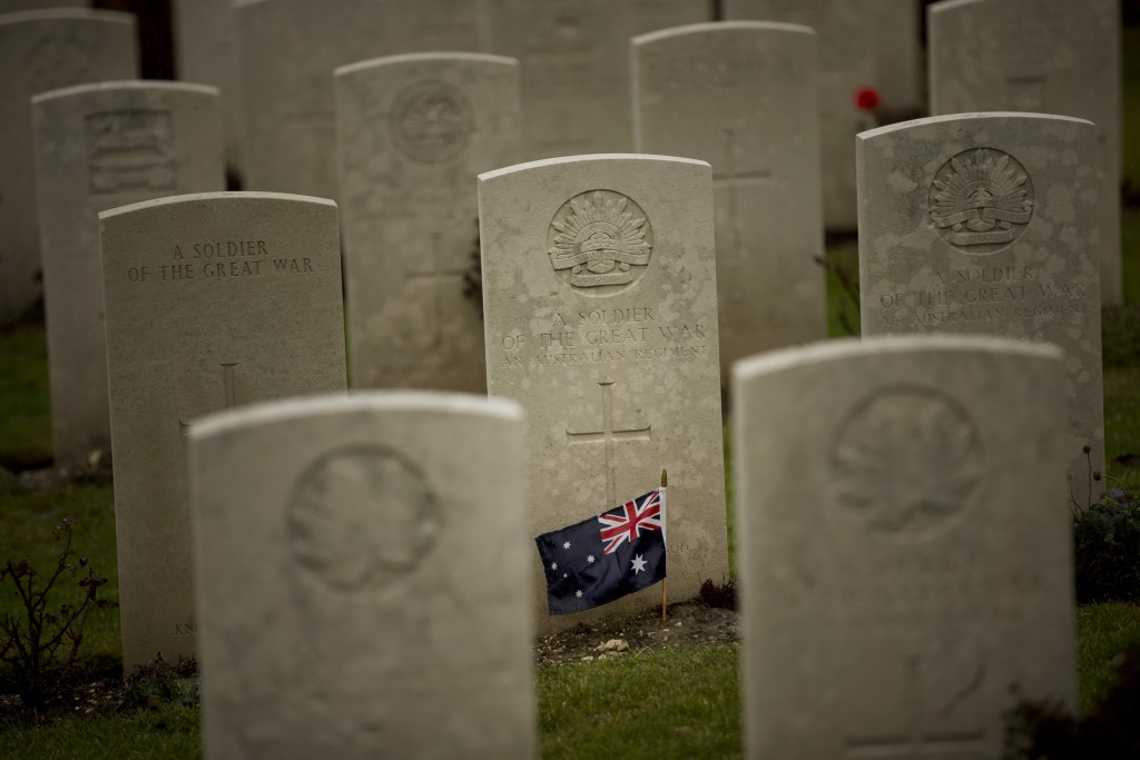 An Australian flag adorns the headstone of an unknown soldier at the World War I Australian National Memorial in Villers-Bretonneux, France, Saturday,