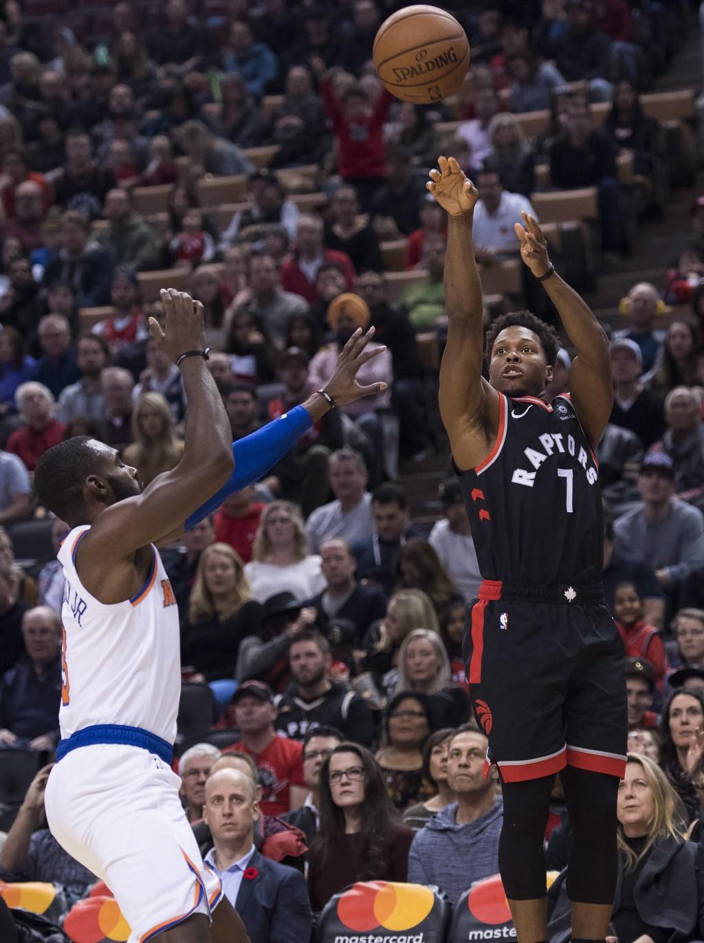Toronto Raptors guard Kyle Lowry (7) shoots past New York Knicks guard Tim Hardaway Jr. (3) during first half NBA basketball action in Toronto on Satu