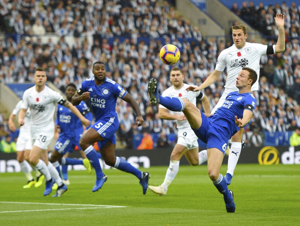 Leicester City's Jonny Evans, right, controls the ball in the air during the English Premier League soccer match between Leicester City and Burnley at