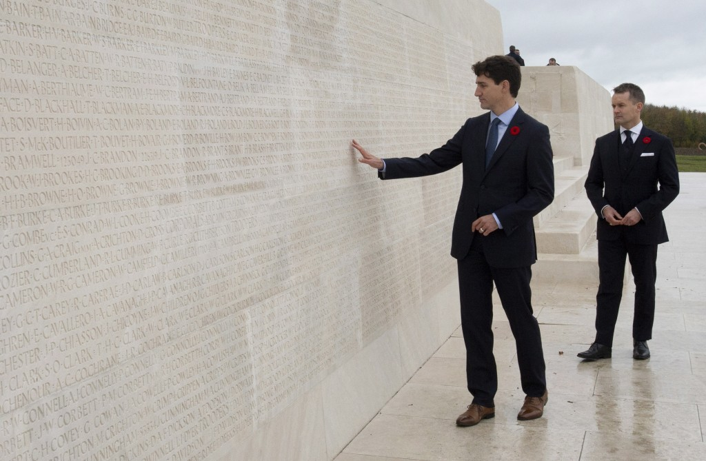 Canada's Minister of Veterans Affairs Seamus O'Regan looks on as Canadian Prime Minister Justin Trudeau touches the names of fallen soldiers engraved