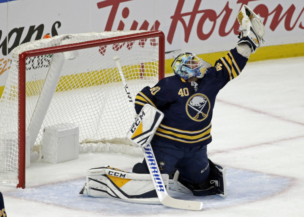 Buffalo Sabres goalie Carter Hutton (40) makes a glove save during the first period of an NHL hockey game against the Vancouver Canucks, Saturday, Nov