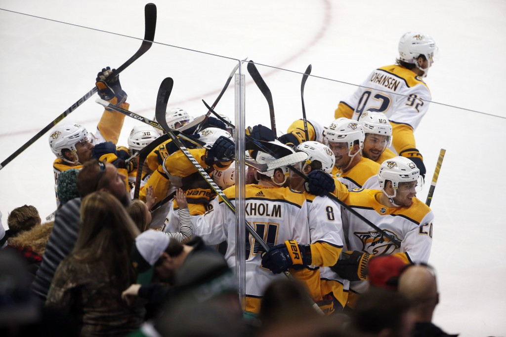 Nashville Predators defenseman Mattias Ekholm (14) is swarmed by teammates after his game-winning goal against the Dallas Stars during overtime of an
