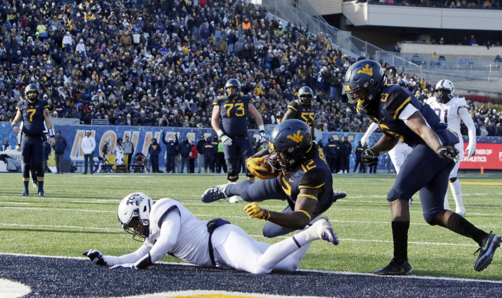 West Virginia wide receiver Gary Jennings Jr. (12) jumps over TCU linebacker Arico Evans (7) to score a touchdown during the second half of an NCAA co
