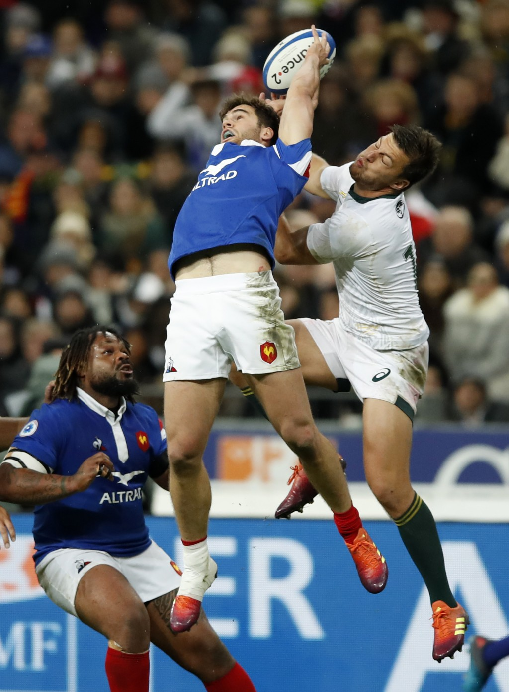 France's Damian Penaud and South Africa's Handre Pollard, right, leap to catch the ball during their rugby union international at the Stade de France