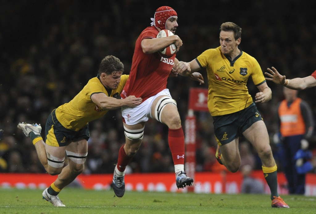 Wales Cory Hill runs between Australia's Dane Haylett-Petty, right, and Michael Hooper during the rugby union international match between Wales and Au