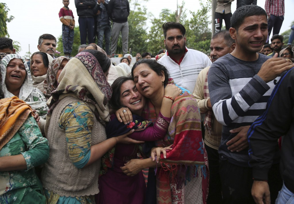 In this Nov. 11, 2018, file photo, family members and villagers grieve and console each other as the body an Indian Army soldier Varun Katal is brough...