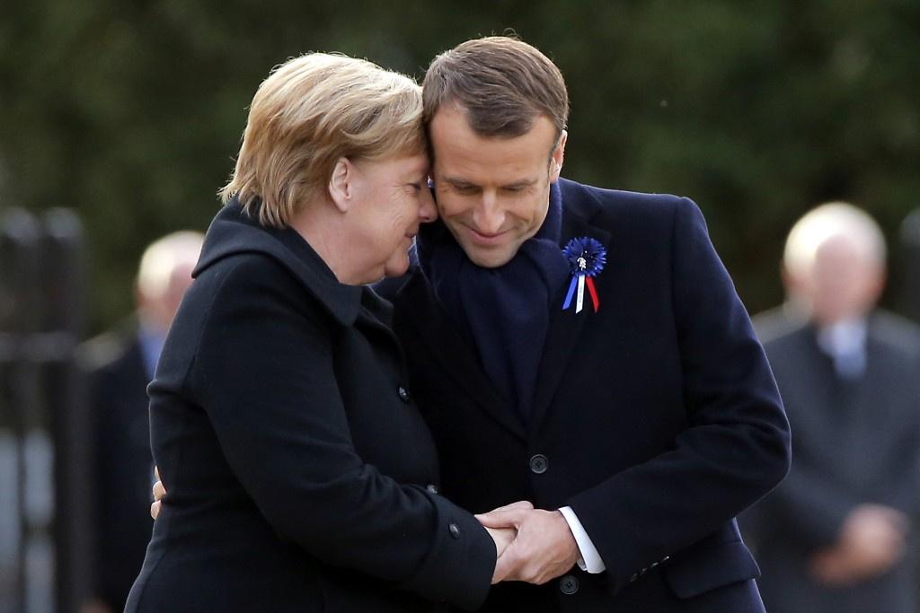 French President Emmanuel Macron, right, holds the hands of German Chancellor Angela Merkel during a ceremony in Compiegne, north of Paris, Saturday,