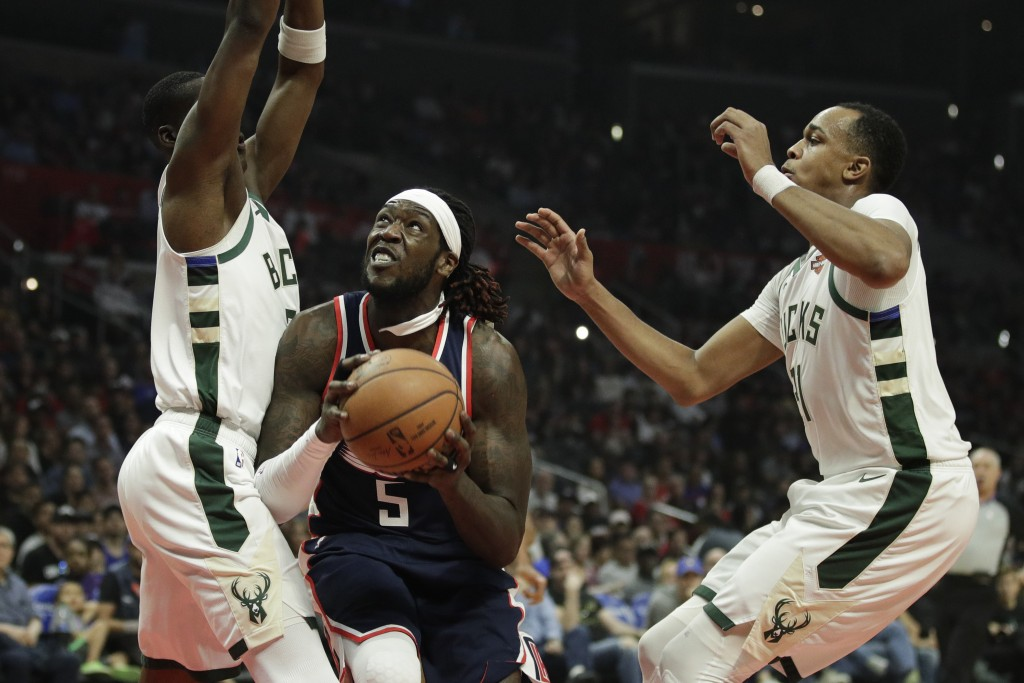 Los Angeles Clippers' Montrezl Harrell, center, looks to shoot under pressure by Milwaukee Bucks' Tony Snell, left, and John Henson during the first h