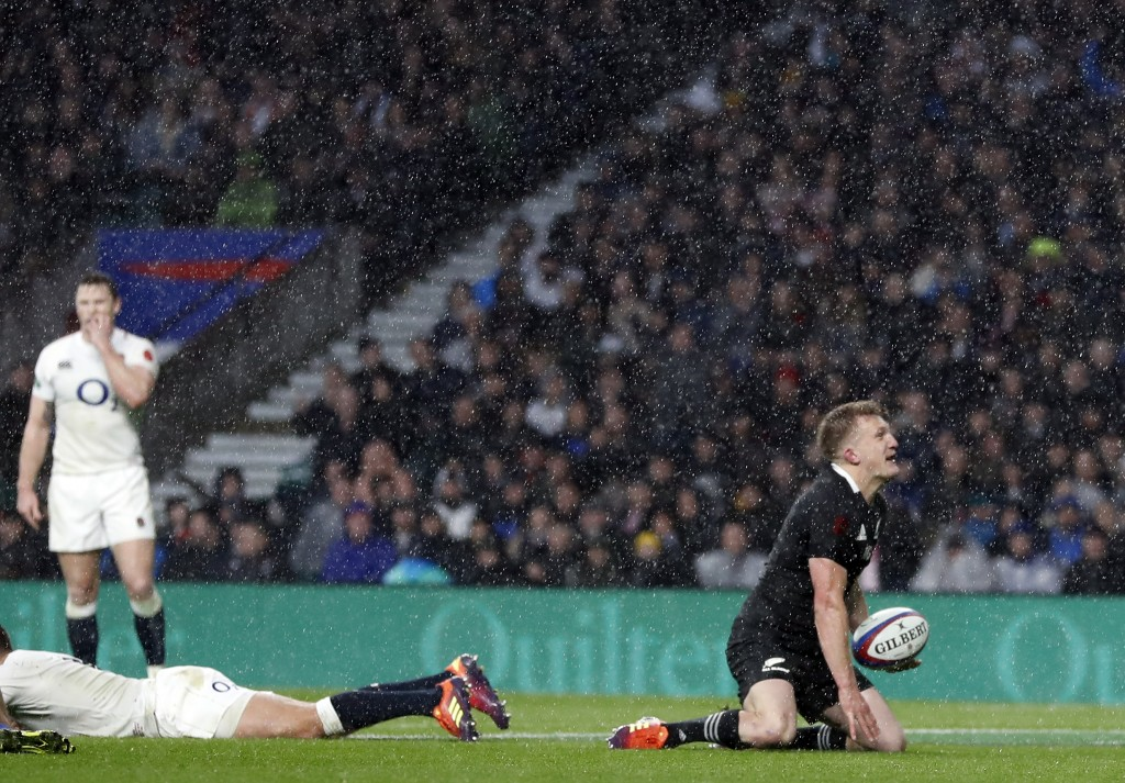 New Zealand's Damian McKenzie, right, score a try during the rugby union international match between England and New Zealand at Twickenham stadium in