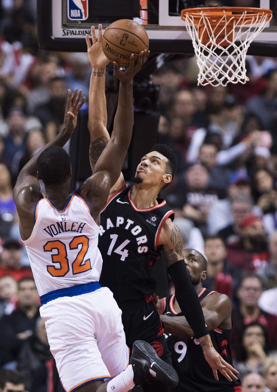 Toronto Raptors guard Danny Green (14) tries to block New York Knicks forward Noah Vonleh (32) during first half NBA basketball action in Toronto on S
