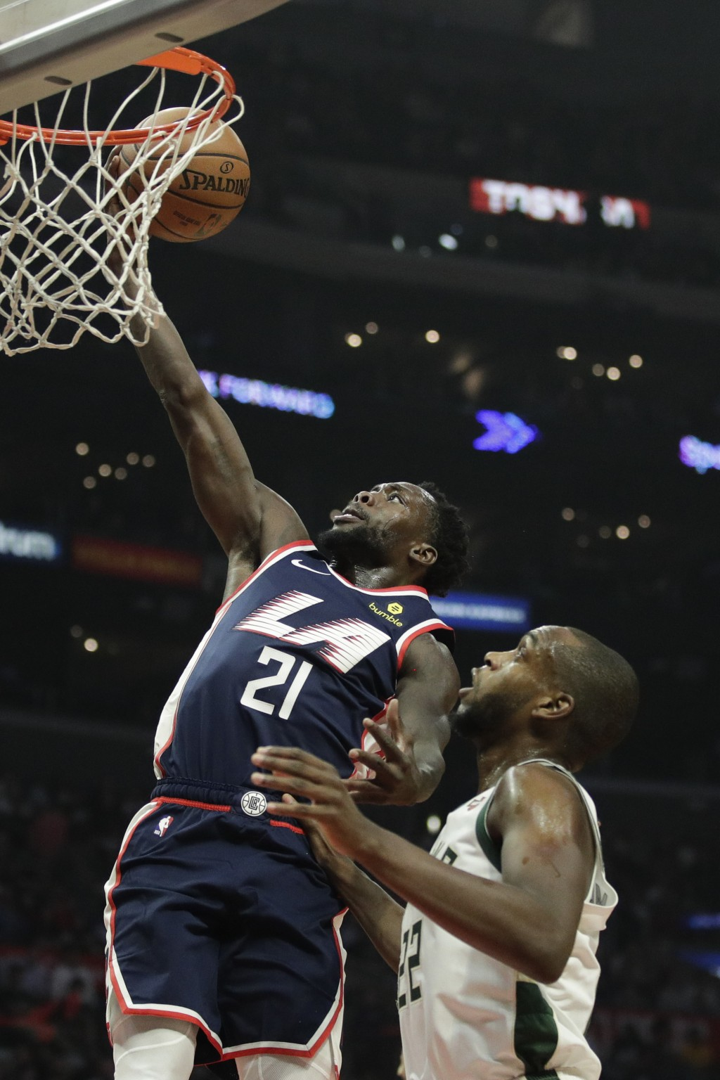 Los Angeles Clippers' Patrick Beverley, left, puts up a shot as Milwaukee Bucks' Khris Middleton looks on during the first half of an NBA basketball g