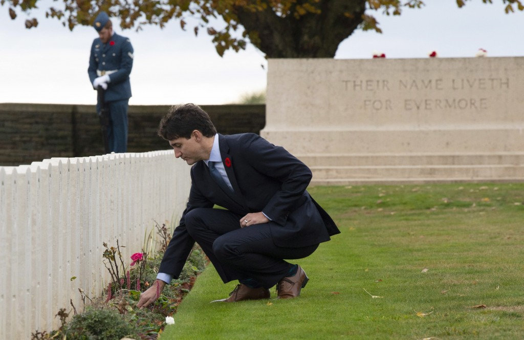 Canadian Prime Minister Justin Trudeau places a flower at a gravestone as he tours the Canadian Ceremony No. 2 near Vimy Ridge, France, Saturday Nov.