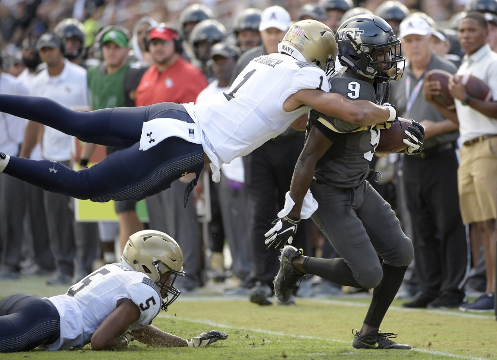 Central Florida running back Adrian Killins Jr. (9) is tackled by Navy safety Jacob Springer (1) after rushing for yardage as defensive back Michael M