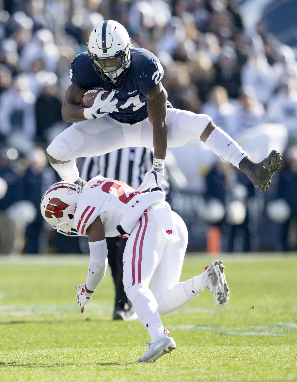 Penn State running back Miles Sanders hurdles Wisconsin's Faion Hicks during an NCAA college football game Saturday, Nov. 10, 2018, in State College,