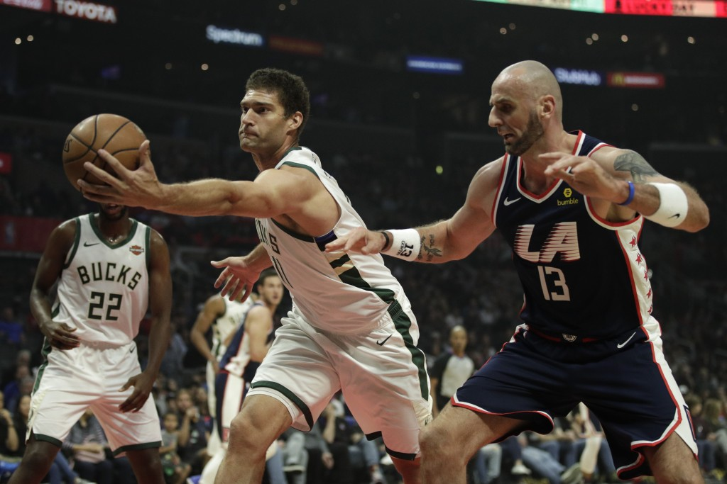 Milwaukee Bucks' Brook Lopez, left, grabs a rebound against Los Angeles Clippers' Marcin Gortat during the first half of an NBA basketball game Saturd