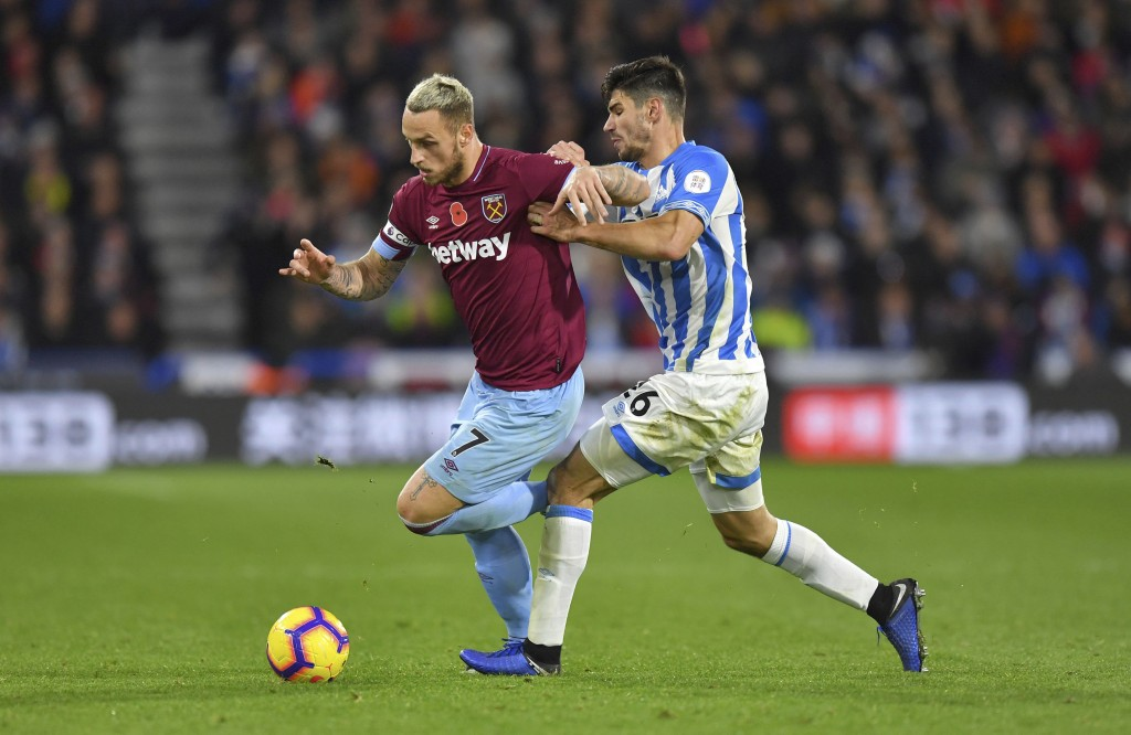 West Ham United's Marko Arnautovic, left, and Huddersfield Town's Christopher Schindler battle for the ball during the English Premier League soccer m