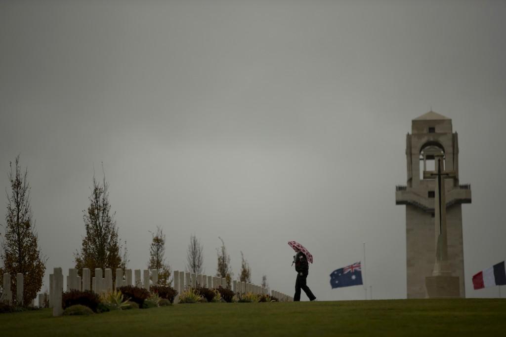 A man walks near headstones at the World War I Australian National Memorial in Villers-Bretonneux, France, Saturday, Nov. 10, 2018. The memorial walls