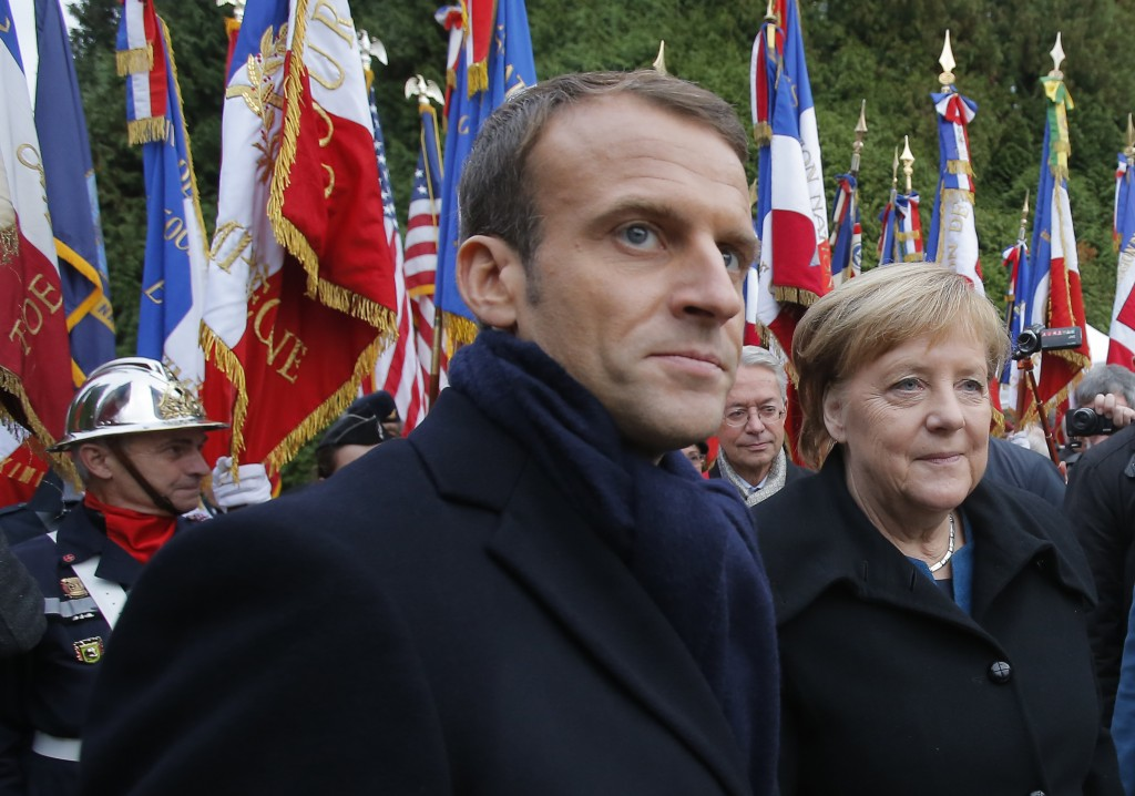French President Emmanuel Macron, center, and German Chancellor Angela Merkel attend a ceremony in Compiegne, north of Paris, Saturday, Nov. 10, 2018.