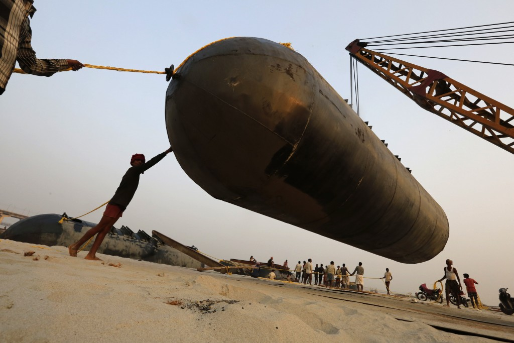In this Monday, Nov. 12, 2018, file photo, Indian laborers pull a pontoon buoy as they build a floating pontoon bridge over the river Ganges for the u