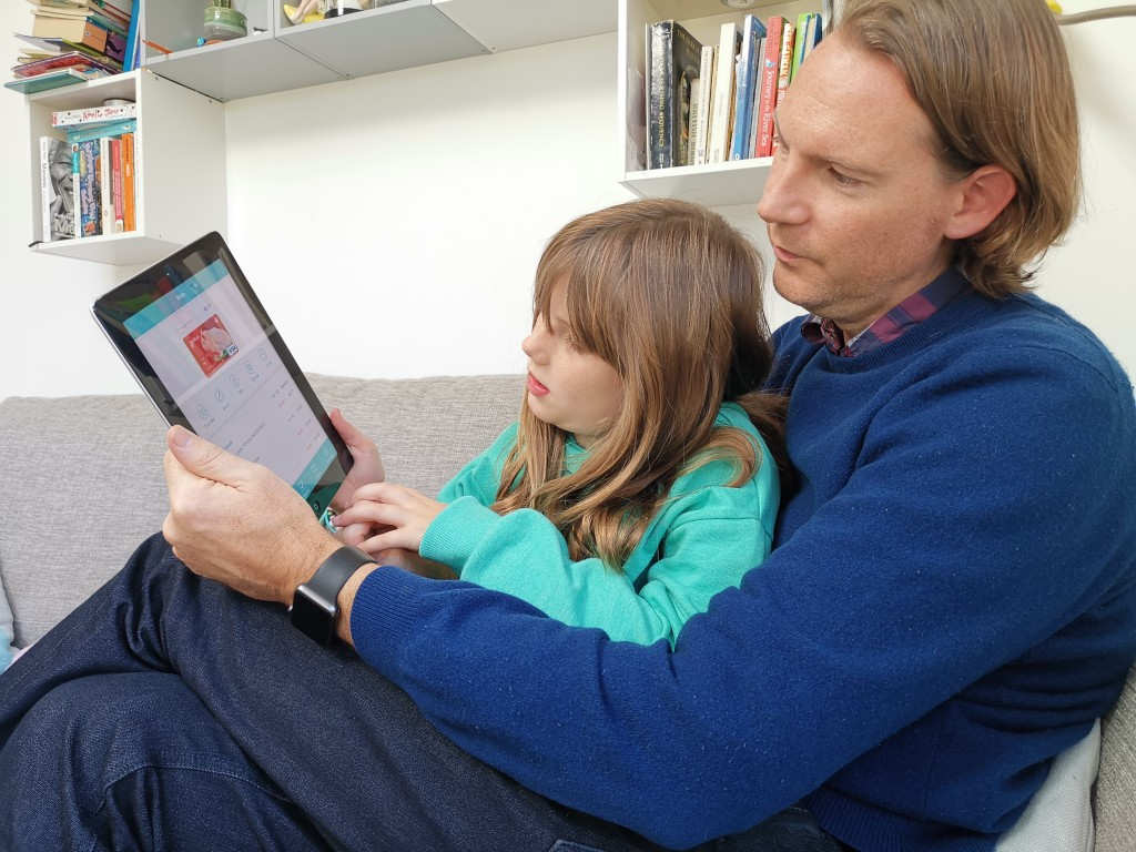 In this photo taken Oct. 21, 2018, Paddy Kelly and his daughter Ailish use Gohenry, one of a wave of digital banking apps for children, in London. A w...