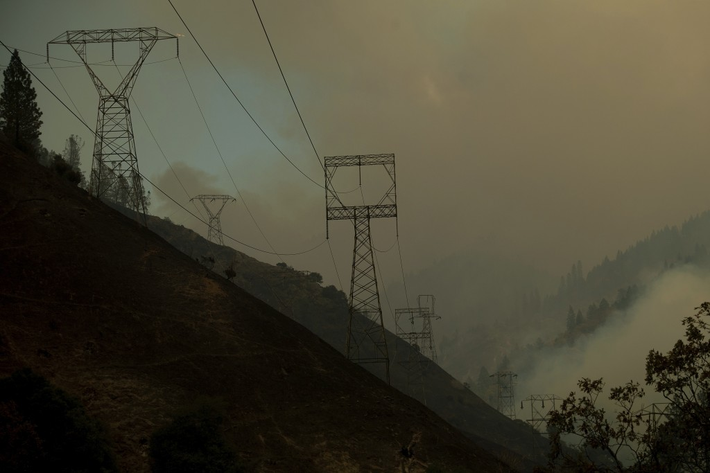 Power transmission lines crest a hilltop above Camp Creek Road, the point of origin of the Camp Fire, in Pulga, Calif., on Sunday, Nov. 11, 2018. (AP